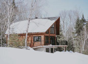 drewniany dom przysypany śniegiem